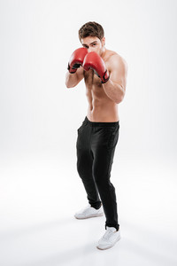 Image of strong young man boxer standing over white background. Look at camera.