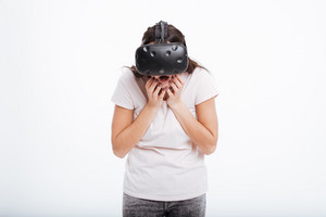 Image of surprised happy woman wearing virtual reality device over white background.
