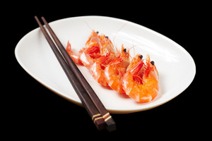 Image of tasty shrimps lying in row with two chopsticks near by