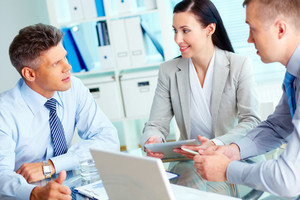 Image of three confident business partners interacting at meeting
