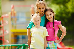 Image of three cute girls looking at camera with smiles outdoors