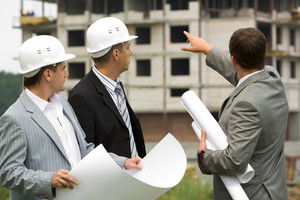 Image of three workers looking construction during discussion of architectural project