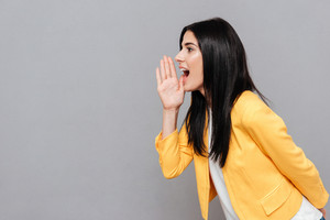 Image of woman dressed in yellow jacket shouting over grey background. Look aside.
