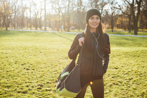 Image of woman runner in warm clothes and earphones in autumn park. Look aside. Holding bag.