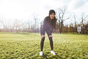 Image of woman runner in warm clothes and earphones in autumn park