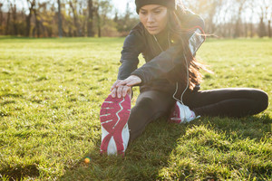 Image of woman runner in warm clothes and headphones in autumn park make sport exercise