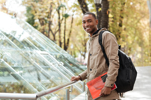 Image of young african cheerful man wearing backpack standing in the street while holding book and look at camera.