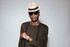 Image of young african man wearing hat and glasses standing in studio. Isolated over grey background.