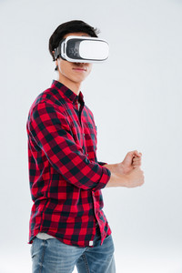 Image of young asian man dressed in casual shirt in a cage and wearing virtual reality device. Isolated over white background.