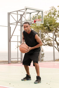 Image of young attractive african basketball player practicing in the street with basketball hoop at background. Looking at camera.