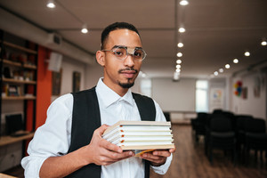 Image of young attractive african businessman wearing eyeglasses standing in library while holding notebooks. Look at camera.