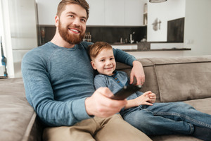 Image of young bearded father holding remote control while watching TV with his little cute son.