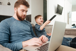 Image of young bearded father using laptop computer while his little son watching TV.