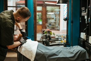 Image of young bearded man getting beard shaving by hairdresser while lies in chair at barbershop.