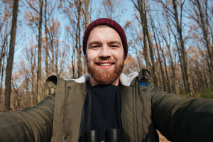 Image of young bearded man making selfie in the forest. Looking at camera and smile.