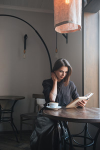 Image of young beautiful woman sitting at the table in cafe and reading book.