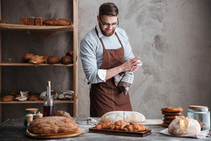 Image of young cheerful bearded man wearing glasses baker standing near a lot of bread. Looking aside.