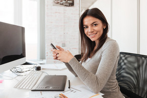 Image of young cheerful businesswoman using computer and phone in office. Look at camera.