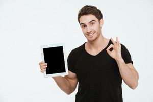Image of young cheerful man dressed in black t-shirt standing over white background showing display of tablet computer while make okay gesture.
