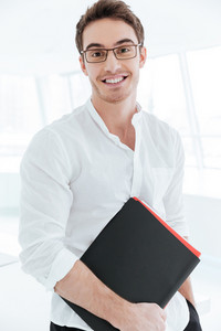 Image of young cheerful man dressed in white shirt holding folder. Looking at camera.