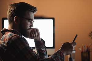 Image of young concentrated bearded web designer dressed in shirt in a cage print and wearing glasses chatting by phone late at night.