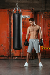 Image of young concentrated boxer posing in a gym with punchbag. Looking down.