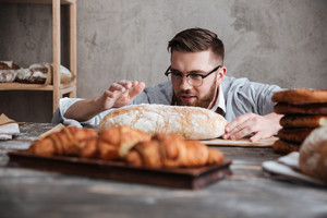 Image of young concentrated man baker standing at bakery near bread. Looking aside.