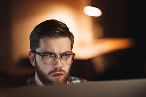 Image of young confused bearded web designer dressed in shirt in a cage print and wearing glasses working late at night and looking at computer.