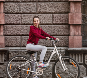 Image of young cute girl dressed in sweater walking with her bicycle in the city while standing near wall. Look at camera.