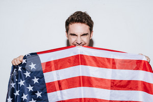 Image of young emotional man posing at studio and look at camera while holding USA flag. Isolated over white background.