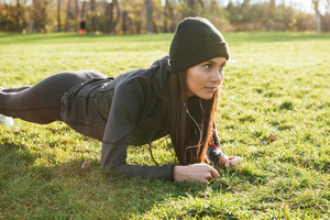 Image of young fitness lady in warm clothes and headphones in autumn park make plank