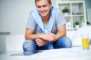 Image of young guy in casual sitting on sofa and looking at touchpad