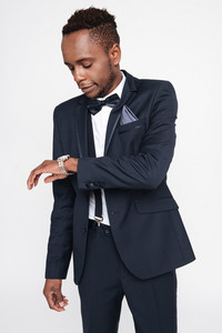 Image of young handsome african businessman posing in studio. Isolated over white background. Look at watch.