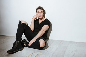 Image of young handsome man dressed in black t-shirt sitting over white background and talking by phone.