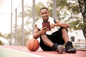 Image of young happy african basketball player sitting in the park near basketball and holding tablet. Look at tablet