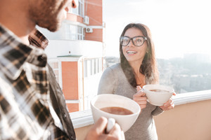 Image of young happy couple drinking coffee while standing on roof. Look at each other.