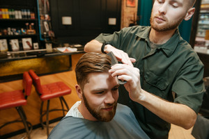 Image of young hipster man getting haircut by hairdresser while sitting in chair.
