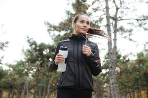 Image of young lady runner in warm clothes and headphones looking aside in autumn park while holding bottle of water and running