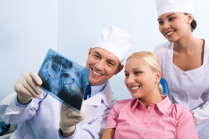 Image of young lady with dentist showing her x-ray photography