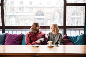 Image of young laughing woman and bearded man friends sitting in cafe and talking while drinking coffee.