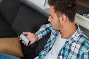 Image of young man dressed in shirt in a cage print sitting on sofa in home and looking at phone.