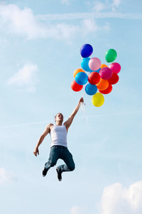 Image of young man jumping and holding colorful balloons