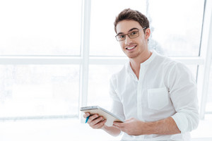 Image of young man wearing eyeglasses and dressed in white shirt holding tablet computer over big white window background. Looking at camera.