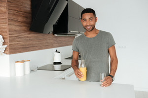 Image of young man with glass of juice standing in the kitchen. Look at the camera.