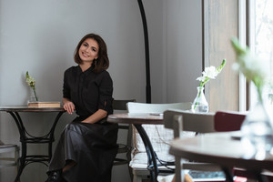 Image of young pretty lady sitting near window in cafe and looking at camera.