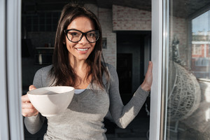 Image of young pretty woman wearing eyeglasses drinking coffee indoors. Look at camera.