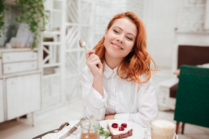 Image of young redhead pretty woman eating cake in cafe while drinking coffee. Look aside.