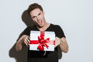 Image of young screaming man dressed in black t-shirt sitting over white background holding gift.