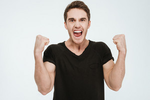 Image of young screaming man dressed in black t-shirt standing over white background make winner gesture.