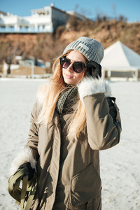 Image of young serious lady wearing sunglasses walks in winter beach with dog on a leash.